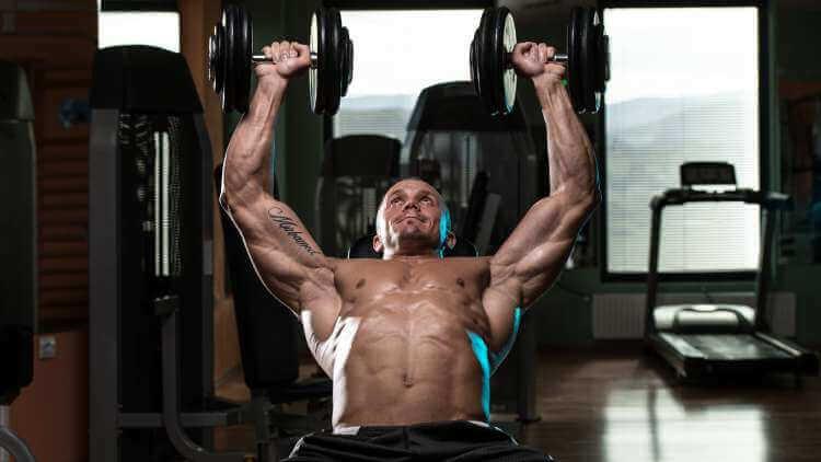 Muscular man doing incline dumbbell press